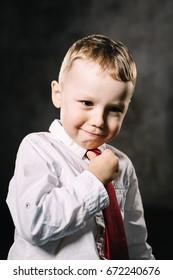 Little boy emotions. Serious Straightening a tie