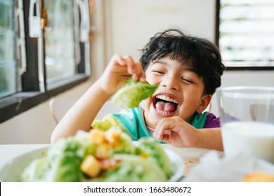 Kleiner Junge genießt mit den Cos in Salat für sein Frühstück.