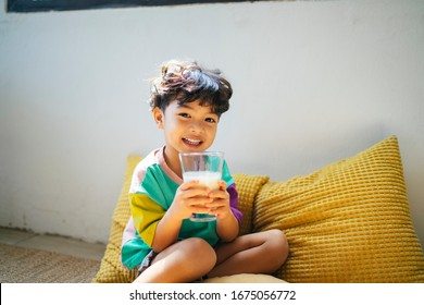 Little boy enjoy drinking the milk in clear glass with happiness.