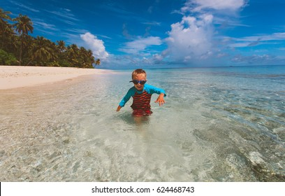little boy enjoy play with water on beach