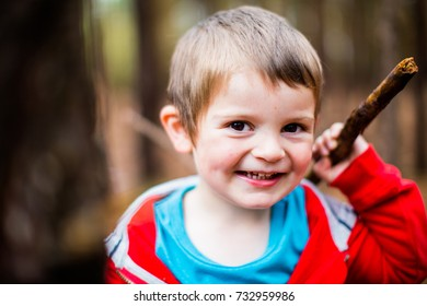 Little boy enjoying playing in the woods forest