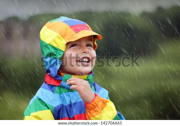 Little boy enjoying the rain dressed in a rainbow colored raincoat