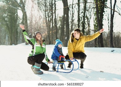 Little boy enjoying a sleigh ride. Child sledding with young mom and dad. Toddler kid riding a sledge. Children play outdoors in snow. Kids sled in winter park. Outdoor active fun for family vacation.