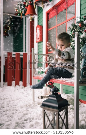 27a6f455329a Little boy enjoying sleigh ride. Cute boy wearing christmas style sweater.  Green wooden wall