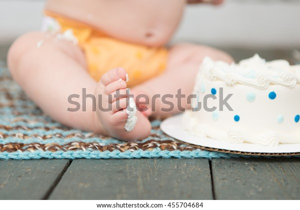 Little boy enjoys eating first birthday cake
