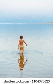 Little boy entering into the Dead sea water for relaxing and enjoying. Family healthy vacation concept