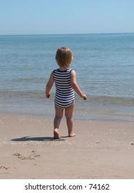 Little boy entering the sea.