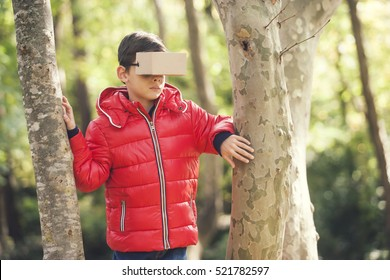 Little boy experiencing virtual reality with cardboard headset in the woods