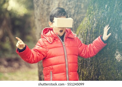 Little boy experiencing virtual reality with a DIY cardboard headset in the woods