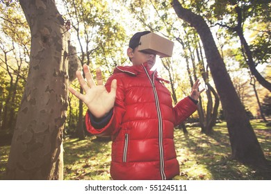 Little boy experiencing virtual reality with a DIY cardboard headset in the woods. (Retro toned backlit soft focus image for vintage effect)