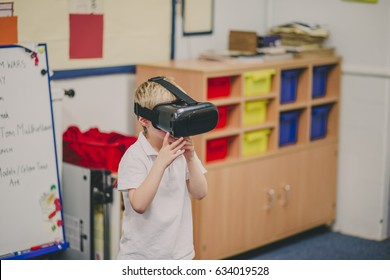 Little boy is experimenting with virtual reality in the classroom at school.