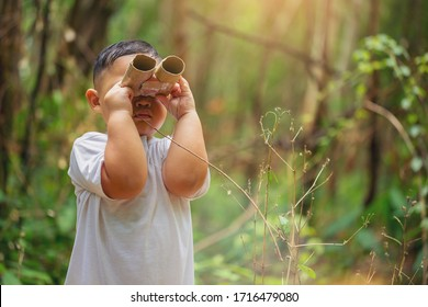 Little boy explorer and adventure with toy binocular at backyard forest