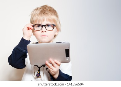 Little boy in eye glasses reading or playing on tablet pc in studio