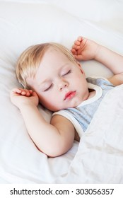 Little Boy with Fair Hair, Raised Hands up Sleeping on a Bed