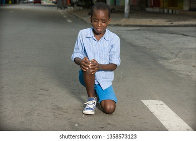 little boy fallen alone on the road crying while holding his injured leg
