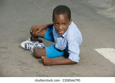 Little boy falling and crying on the road. child lying alone on the road with knee pain lifting his head and waiting for help