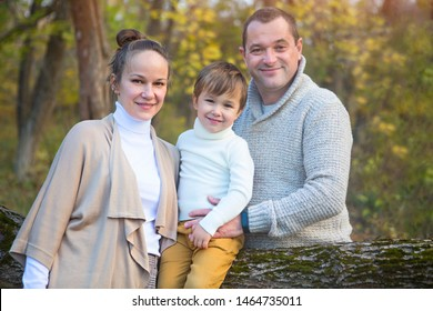 Little boy with family in the park. Father, mother and little son at autumn day