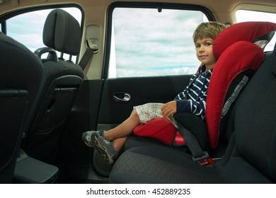 Little boy fasten seat belt in high back booster car seat. Child safety.