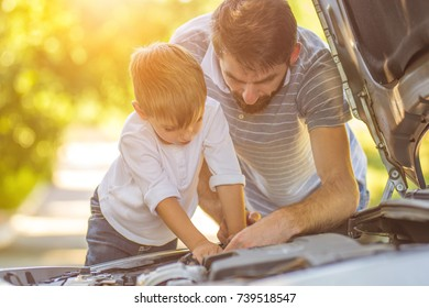 The little boy and the father fixing a car