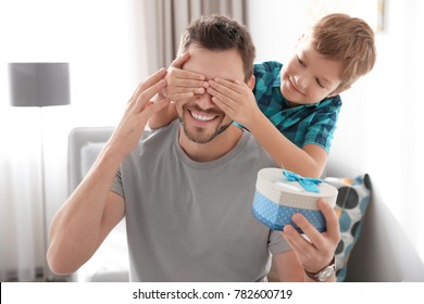 Little boy and father with gift box at home. Father's day concept