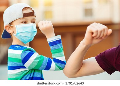 Little boy and father greeting with elbows outdoors. Coronavirus prevention. Elbow greeting style. Family, lifestyle, new style of greetings. Coronavirus quarantine. Social distancing concept. Family.