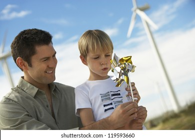 Little boy and father playing with paper windmill at windmill farm