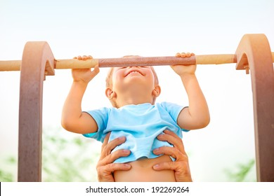 Little boy with fathers help catch up on the horizontal  bar, active childhood, cute small acrobat, workout on backyard, summer camp concept