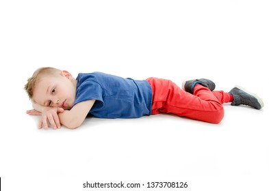 Little boy feels annoyed grumpy lying on the floor. Isolated on white background