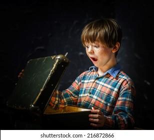 Little boy finding treasure inside a suitcase