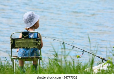 Little boy with fishing rod sitting near the lake