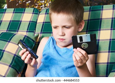 Little boy with floppy disk and audio cassette outdoors