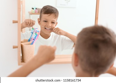 Little boy flossing teeth in bathroom