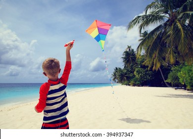 Little boy flying a kite on tropical beach