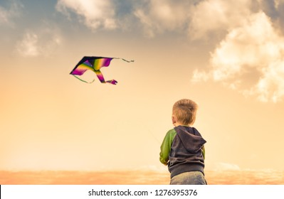 Little boy flying a kite at sunset.