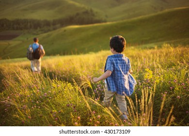 A little boy follows his father on a field