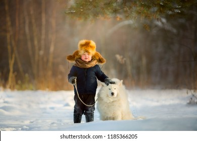 Little boy in fox fur hat portrait with Samoyed dog at winter day