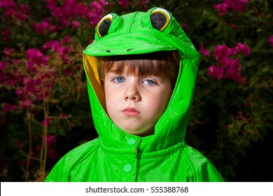 A little boy in a frog raincoat looks unamused at the camera.  He has rain drops all over his coat and it is a dark day.  Behind him is a large bougainvillea bush.