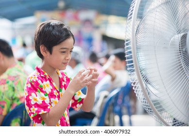 Little boy in front of electric fan in the summer hot time