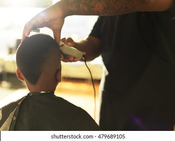 little boy getting hair cut by barber, shot with selective focus and lens flare