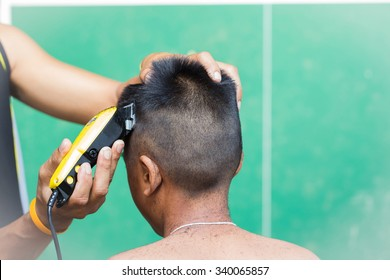 little boy getting his head shaved by farther