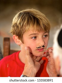 Little boy getting a mustache painted on his face.