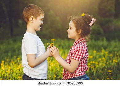 Little Boy gift flowers his friend girl. Valentines day concept.