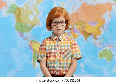 Little boy with ginger hair, wearing checkered shirt and eyeglasses, standing against map background, going to school. Clever pupil standing in cabinet of geography at school, going to have lesson