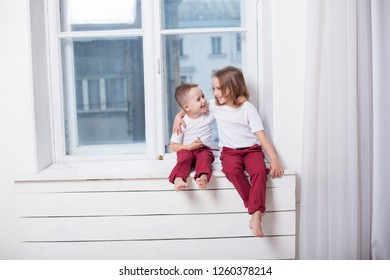 the little boy and girl alone at home watching in the window