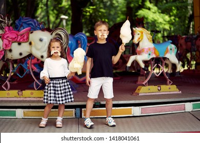 A little boy and girl in an amusement park are eating cotton candy. The boy and girl made a mustache from candyfloss.