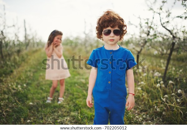 little boy and girl in blooming garden