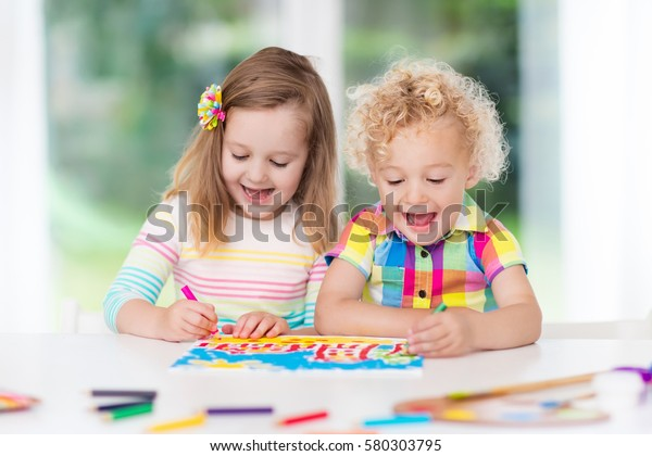 Little boy and girl draw together in white room with window. Kids doing homework, painting and drawing. Children paint with paintbrush color and pencils. Art and crafts for toddler and preschooler