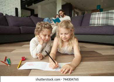 Little boy and girl drawing with color pencils on the floor while parents reading book on couch, siblings playing together, elder sister teaching younger brother, family spending time in living room