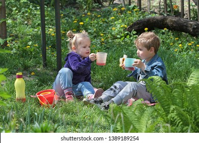 Little boy and girl drink drink sitting on the grass