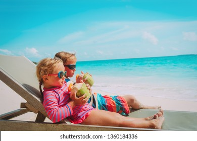 little boy and girl drinking coconut on beach vacation